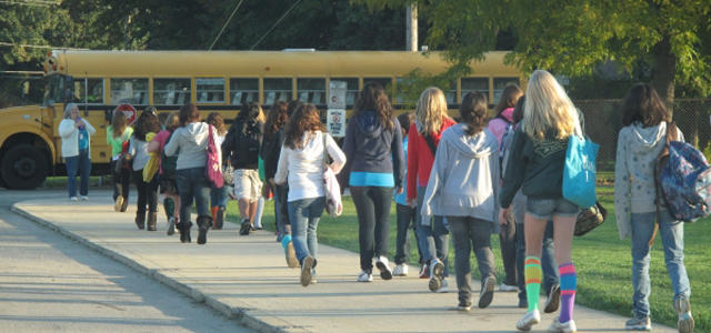 students walking to get on a bus
