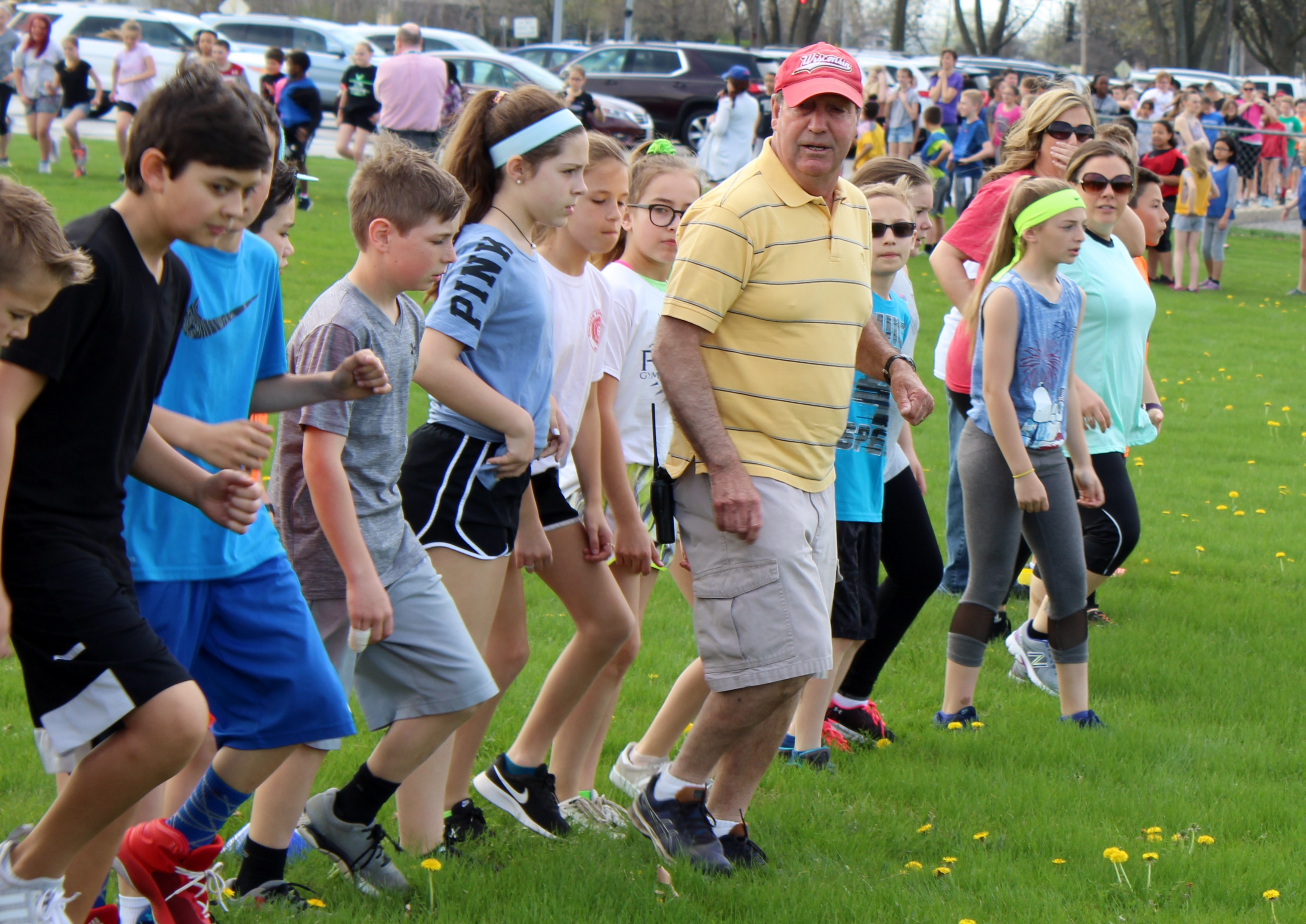 Walker's Grove Elementary School physical education and health teacher Steve Riederer leads students during a 50 yard dash during an all school exercise event on May 2, 2018. Riederer is retiring this year after 45 years in education, including 42 in District 202.