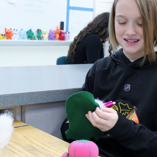 Sixth graders finish hand sewing stuffed monsters, 12.14.2018