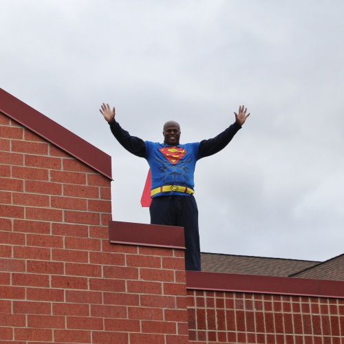 Principal greets students from the rooftop of the school in Superman costume, 10.16.2019