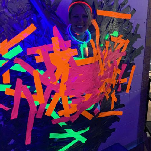 Principal taped to wall to raise money for Glow Run, 10.15.2019